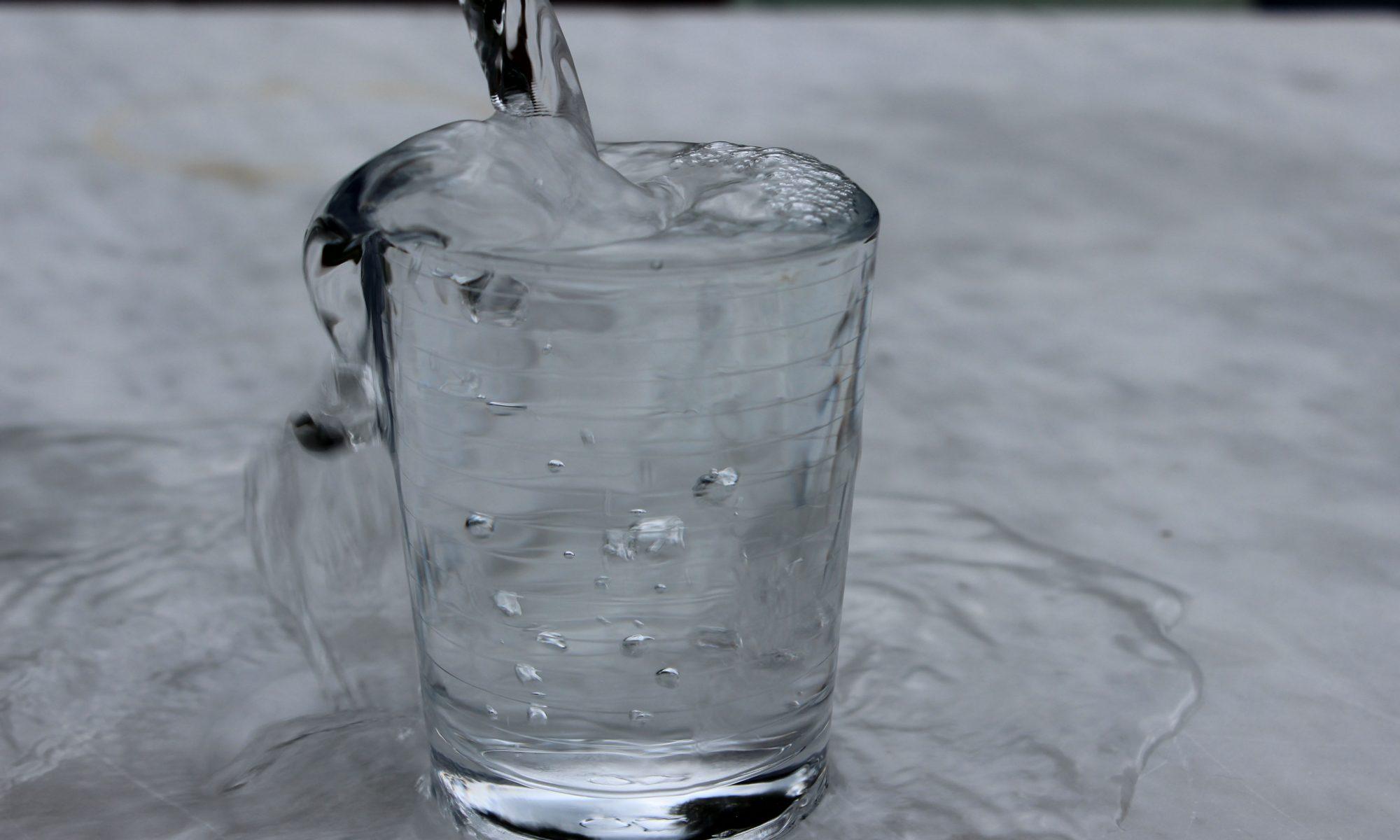 Überlaufendes Glas mit Wasser